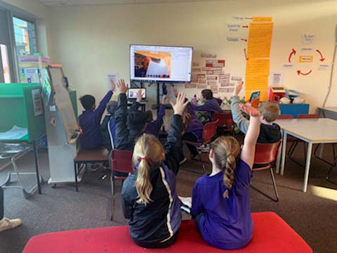 EdConnect Volunteer remotely joins a classroom to read a story in lieu of his regular volunteering sessions due to school closures.