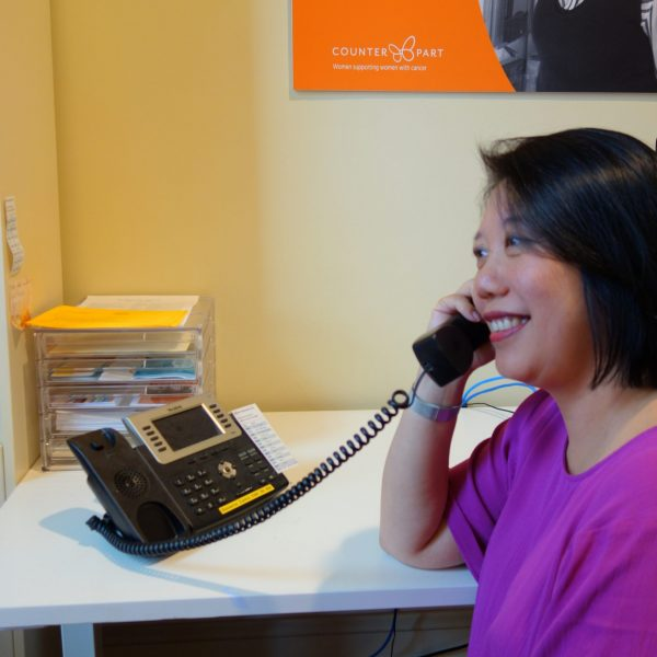 Peer Support Volunteer May on the phone supporting a woman as she navigates her way through a diagnosis of cancer and treatment.